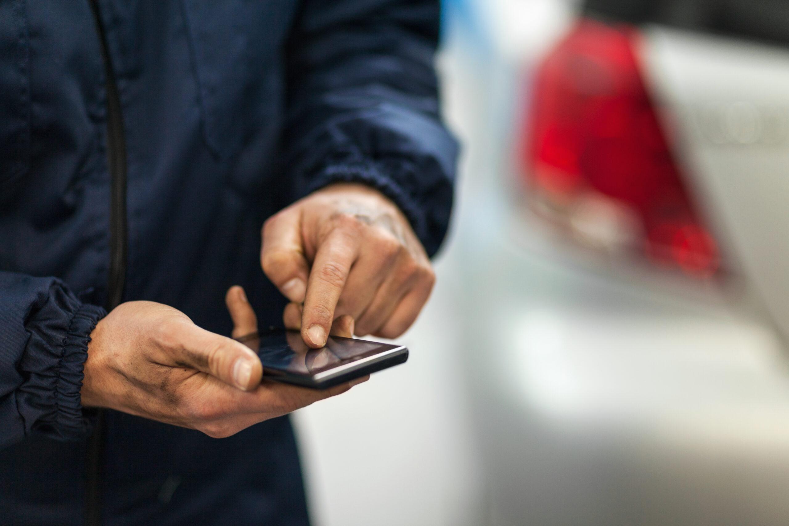 close up of a car mechanic using smart phone in repair shop
